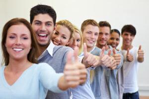 Erfolgreiche Studenten in einer Reihe halten ihre Daumen hoch